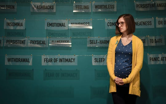 """Melissa Hudecz, a survivor of Larry Nassar and co-curator of """"Finding our Voice: Sister Survivors Speak,"""" stands in front  one of the pieces in the MSU Museum's exhibit that opens Tuesday, April 16 and runs through March of 2020."""