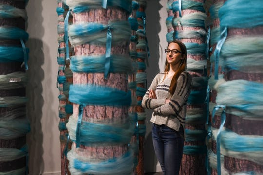 """Katie Black, a survivor of Larry Nassar and co-curator of the Michigan State University Museum's """"Finding Our Voice: Sister Survivors Speak"""" exhibit, stands among makeshift trees with the actual teal bows and ribbons that were hung throughout campus to honor survivors of sexual abuse. The exhibit opens Tuesday, April 16, 2019, and runs through March 2020 in the main gallery and part of the second floor."""