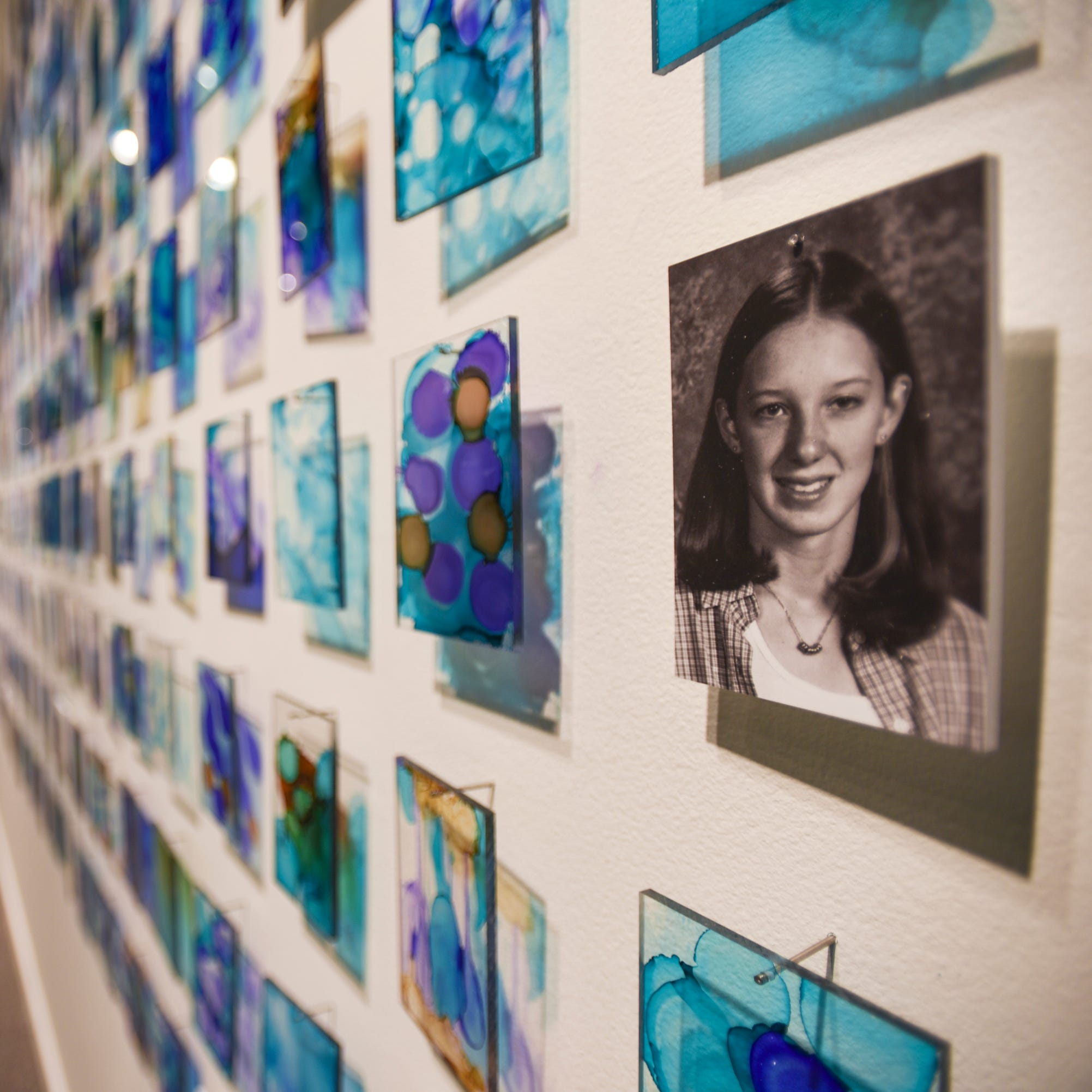 "A wall in the exhibit ""Finding Our Voice: Sister Survivors Speak"" at the MSU Museum shows pictures of young girls and women at the age Larry Nassar began sexually abusing them."
