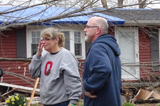 A friend comforts Shelley Carey, whose home at 4497 Plymouth-Springmill Road was damage by a tornado Sunday afternoon.