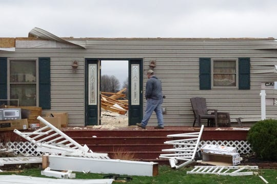 A friend walks through what used to be the front door of Jim Bly's home at 444 Plymouth-Springmill Road near Shelby on Monday. A tornado hit the neighborhood Sunday afternoon.