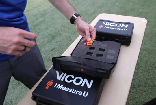 Daniel Greenwood, director of the Human Performance Center at the University of Memphis holds a VICON biometric measuring device, which his team has installed on ankle harnesses to monitor individual player's physical impact stress levels.