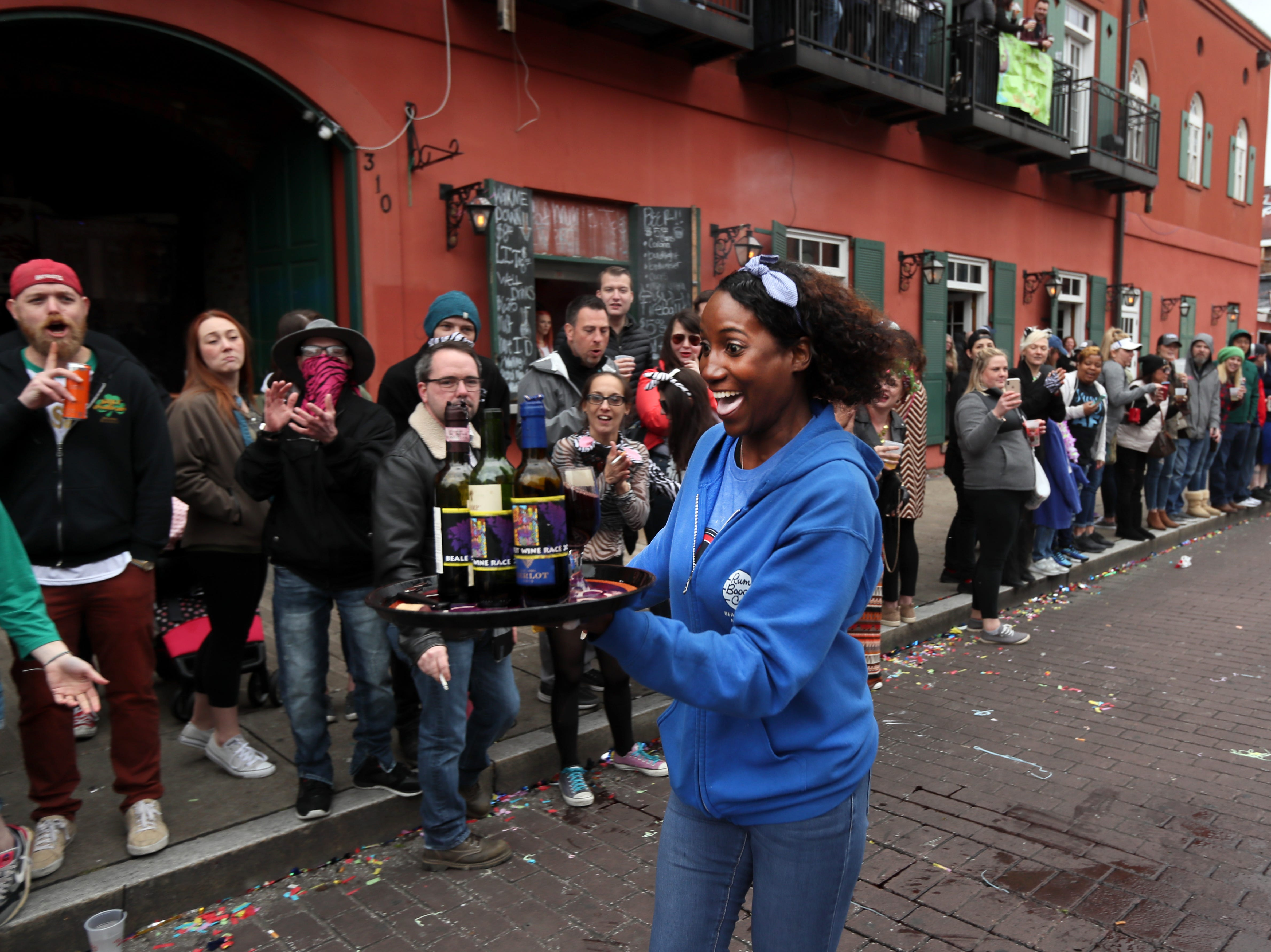 Takena Walton speeds down the street with a tray full of bottles and glassware during the Beale Street Wine Race downtown on Sunday, April 14, 2019.