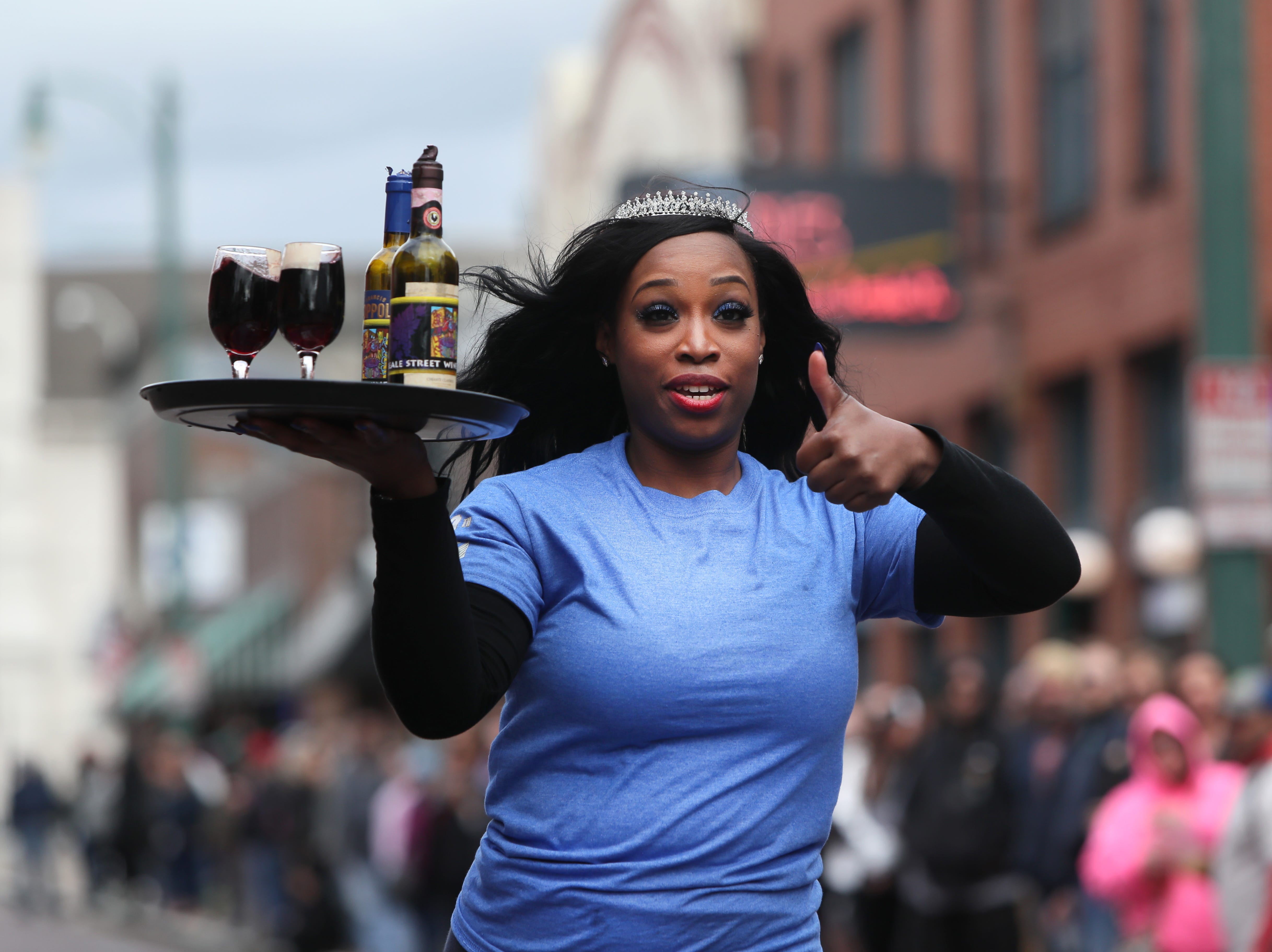 Sherita Thomas speeds down the street with a tray full of bottles and glassware during the Beale Street Wine Race downtown on Sunday, April 14, 2019.