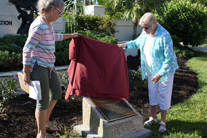 MIFA president Karen Swanker, left, and Mary Ann Sarazen uncover the plaque. Friday morning, the Marco Island Foundation for the Arts unveiled a plaque with the names of donors who have contributed to the purchase of the Double Eagle sculpture at Sarazen Park on Marco.