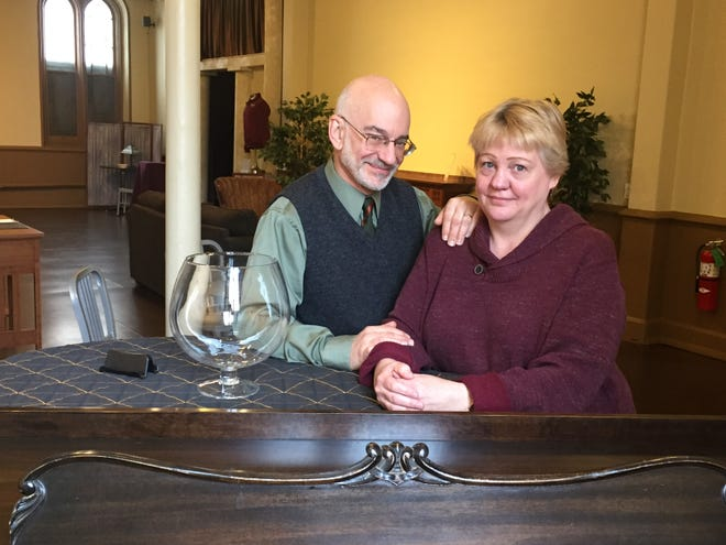 Chris and Jane Flieller lean on the piano in the lobby of the Tenth Street Theatre.