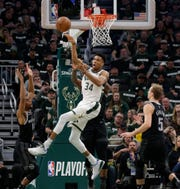 Giannis Antetokounmpo passes out of traffic to an open man.