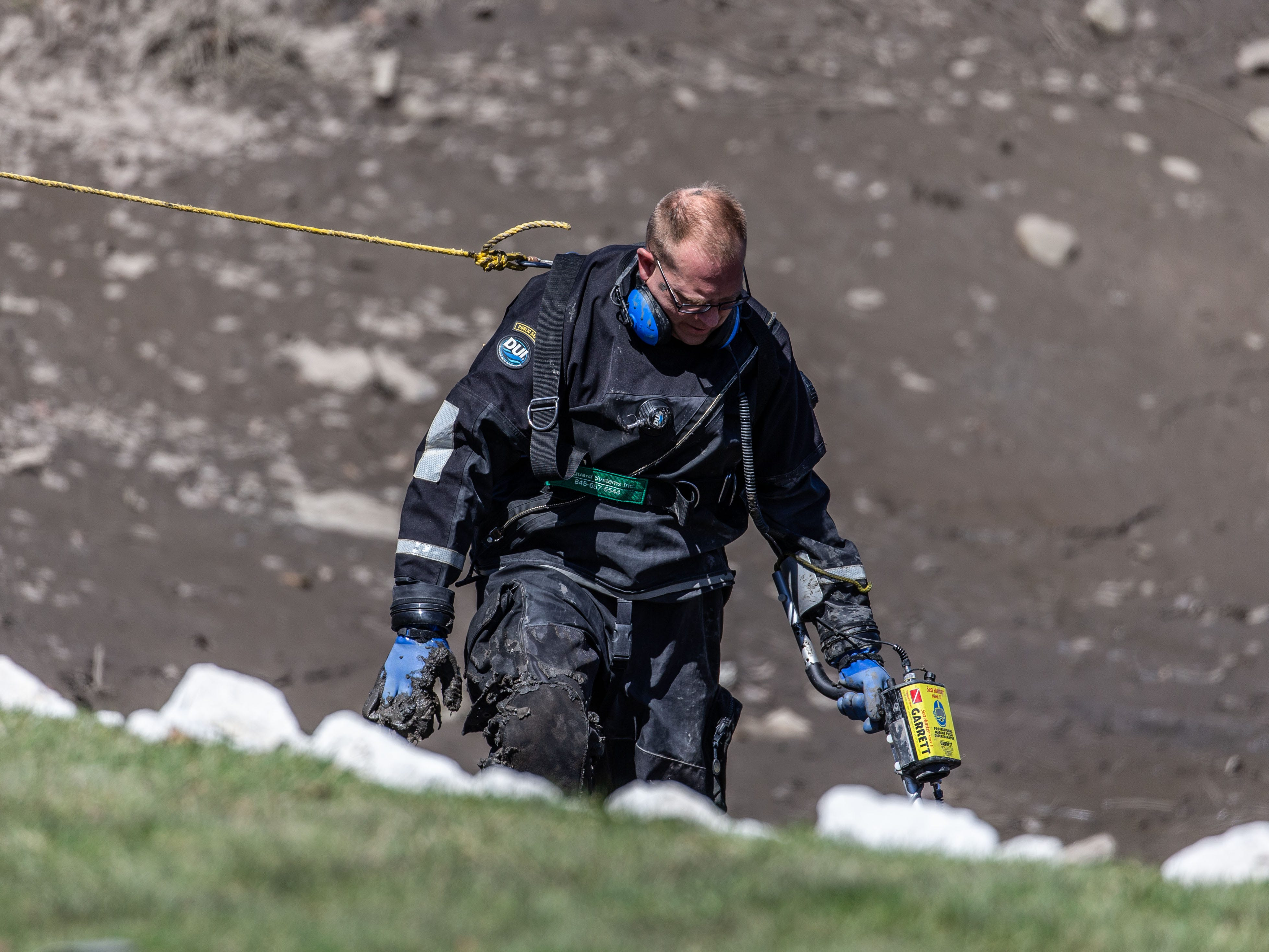 A member of the Waukesha County Sheriff's Dive Team assists the Town of Brookfield Police as they search for evidence in a drained pond at the Brookfield Lake Condominiums on Monday, April 15, 2019. The search is related to a November homicide.
