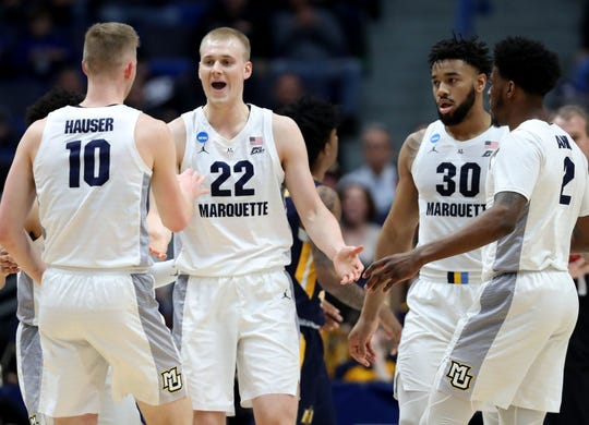 Joey Hauser (22) of the Marquette Golden Eagles celebrates scoring and getting fouled with teammates Sam Hauser (10), Ed Morrow (30), and Sacar Anim #2 during their first round game of the 2019 NCAA Men's Basketball Tournament against the Murray State Racers at XL Center.