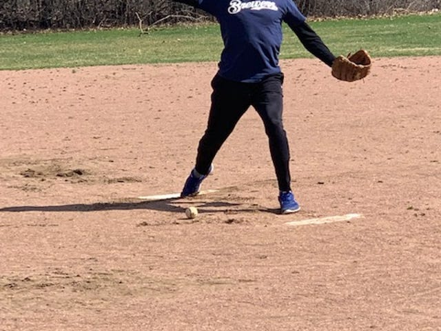 Derek Pipkorn, owner of Mathnasium of Wauwatosa, winds up a practice pitch April 14 in a Wauwatosa park. He will throw out the first pitch for the May 8 Milwaukee Brewers game.