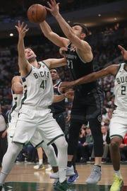 Bucks forward Nikola Mirotic  and Pistons center Zaza Pachulia battle for a rebound Sunday night.