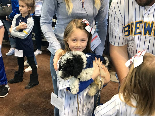 Lola Labodda, a Muskego 6-year-old, holds Yeli at Miller Park on April 15, 2019. The hope is to train the mini doodle to assist with Lola's type-1 diabetes.