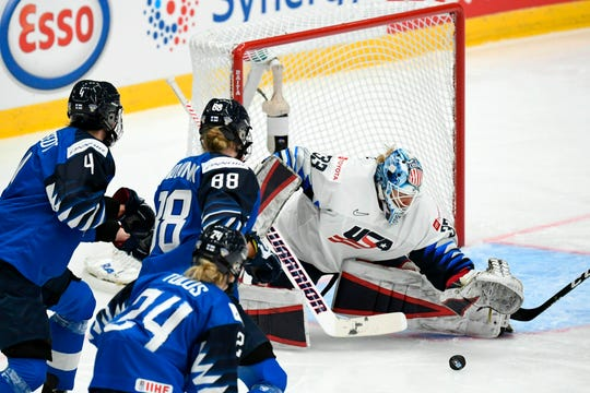 Goalkeeper Alex Rigsby makes a save from Finland's Rosa Lindstedt (left), Ronja Savolainen, and Noora Tulus.