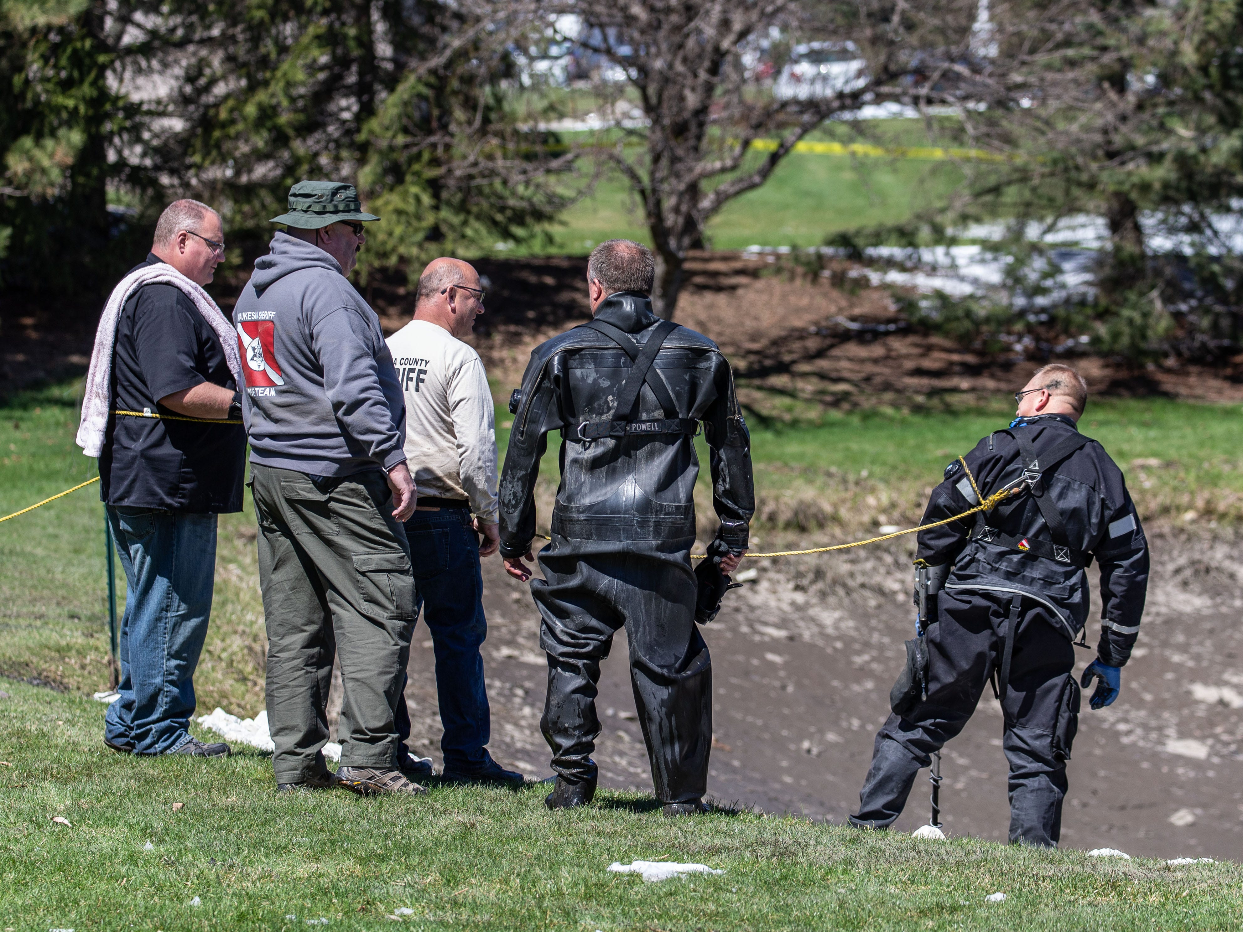 Members of the Waukesha County Sheriff's Dive Team assist the Town of Brookfield Police as they search for evidence in a drained pond at the Brookfield Lake Condominiums on Monday, April 15, 2019. The search is related to a November homicide.