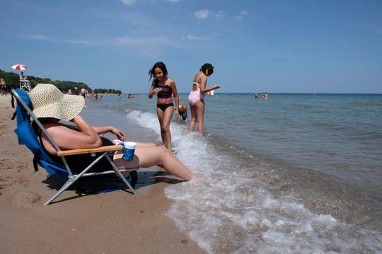 Nadia Elouaski keeps her feet cool on the shores of Lake Michigan during a hot summer heat wave.