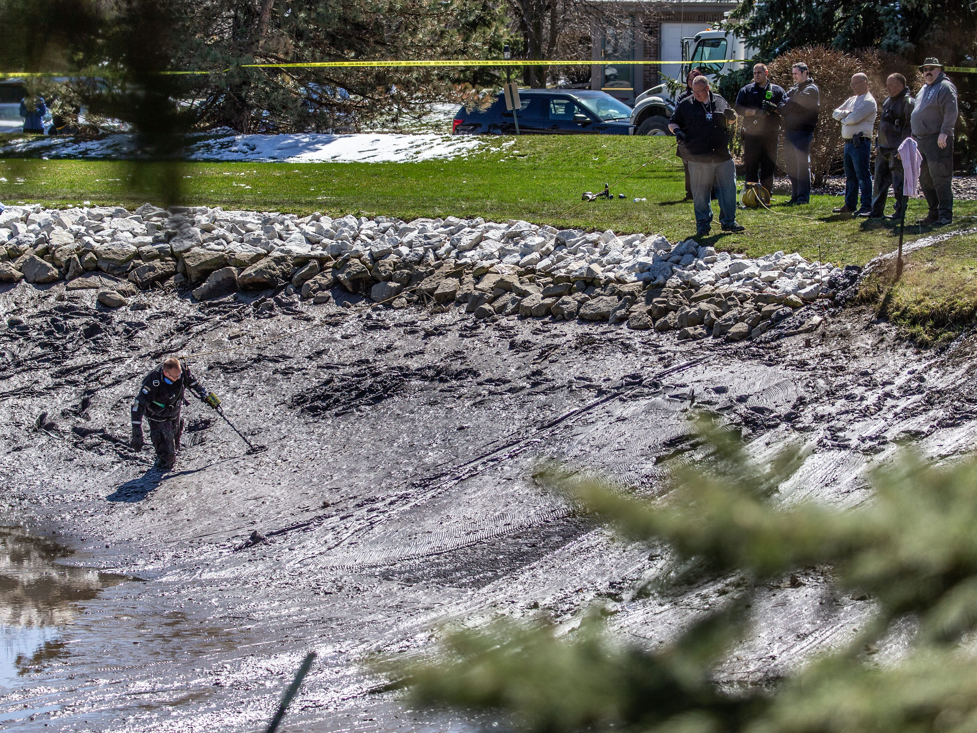 A member of the Waukesha County Sheriff's Dive Team uses a metal detector to search for evidence in a drained pond at the Brookfield Lake Condominiums on Monday, April 15, 2019. The search is related to a November homicide.