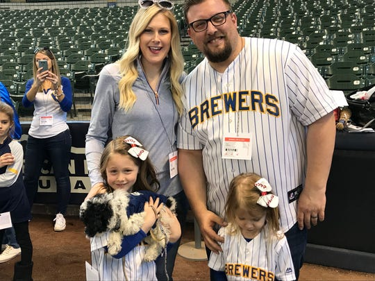 (Clockwise from top left) Jessica Labodda, Michael Labodda, camera-shy Libby, 4, and Lola, 6, pose with their new 11-week-old mini doddle named Yeli at Miller Park on Monday.