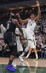 Bucks forward Giannis Antetokounmpo is fouled  by Detroit Pistons center Andre Drummond. Drummond was ejected from the game for a flagrant foul.