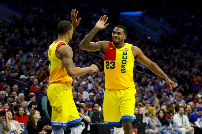 Milwaukee Bucks' George Hill (left) and Sterling Brown celebrate during the second half of the team's NBA basketball game against the Philadelphia 76ers.