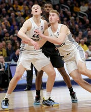 Marquette forward Joey Hauser (22) and Marquette forward Sam Hauser (10) box out Providence guard Alpha Diallo (11) during a free throw attempt during the second half of their 79-68 win over Providence at Fiserv Forum.