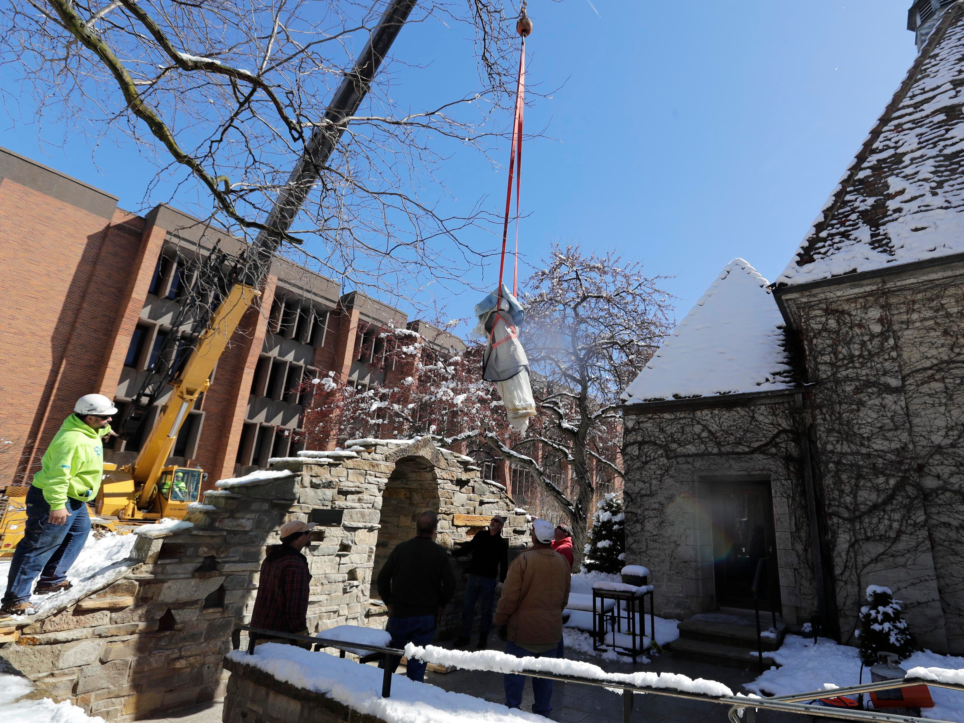 Workers install a statue of Mary in the Grotto of the Blessed Virgin Mary behind the St. Joan of Arc Chapel on the south side of the Marquette University campus Monday. It is meant to be a quiet place of reflection on campus. It was commissioned from the Demetz Art Studio of Ortisei, Italy.