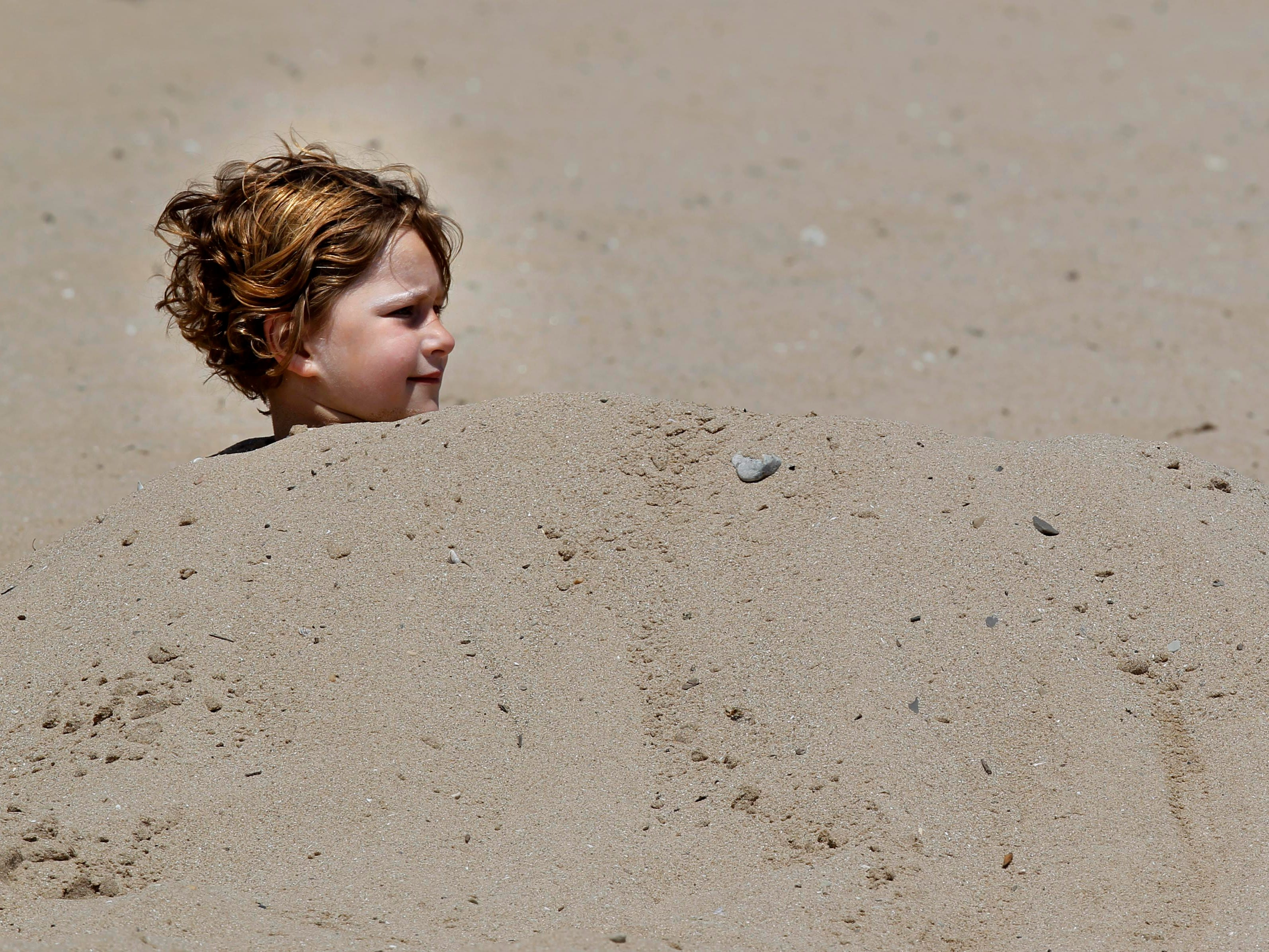 Julia Edler stays cool at at Bradford Beach after being covered in sand by her father, Darin Edler, and sister Alexis.