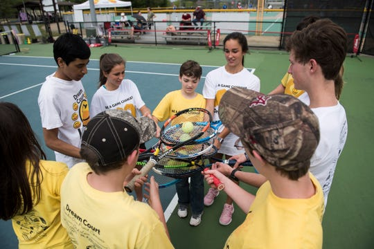 Athletes and volunteers run a drill during Dream Court practice at Thompson Park in Montgomery, Ala., on Saturday, April 13, 2019. Dream Court is a non-profit tennis program for special needs athletes.