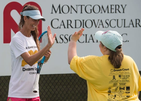 Jessica Weyreuter, founder of Dream Court, high fives Shelby Bullen during practice at Thompson Park in Montgomery, Ala., on Saturday, April 13, 2019. Dream Court is a non-profit tennis program for special needs athletes.