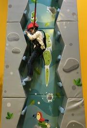 Reid Northam, 5, climbs one of the new rock walls at Newtopia Fun Park.