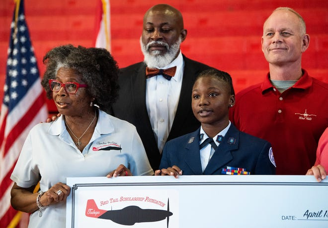 Lee High School student Ty'Asia Brown, center, is presented a $10,000 Red Tail Scholarship for flight training at the Lee campus in Montgomery, Ala., by, from left, Jewell Pitts, Lorenza Pharrams and Col. Will Sparrow on Monday April 15, 2019.