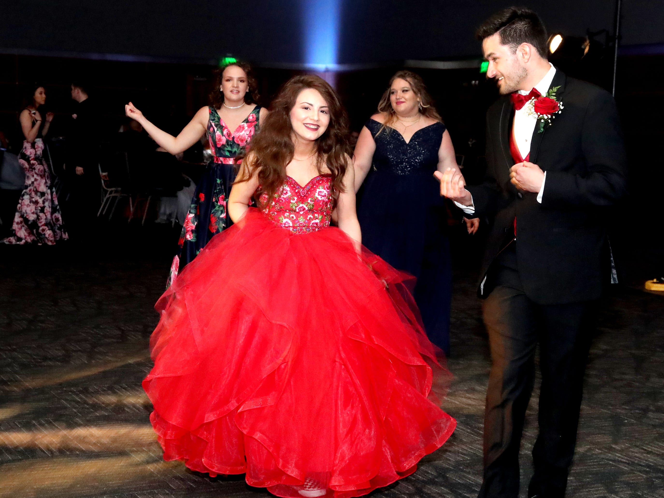 Destiny Smith, left and Alex Ketel, right walk across the dance floor at Blackman's prom held on Friday April 12, 2019, at MTSU.