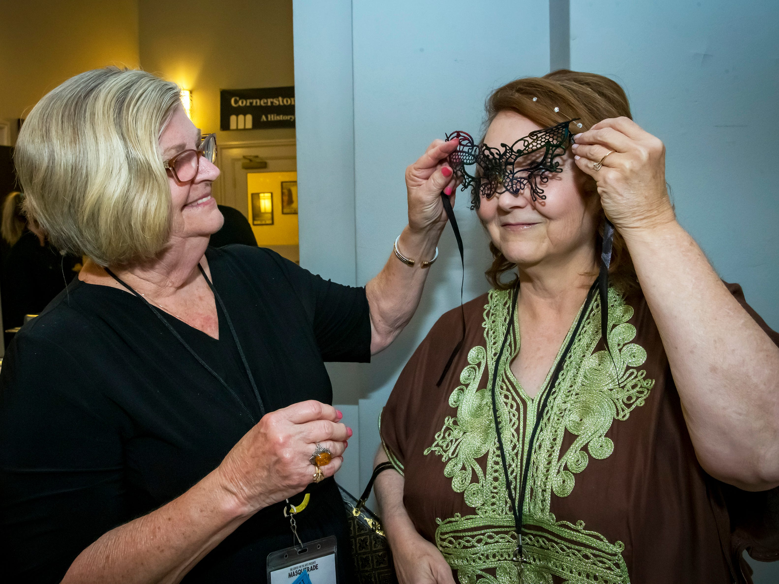 Dianne Kimbrough helps Ginger Jenkins with her mask at the Masquerade Bash at the Center for the Arts on Saturday, April 14, 2019.