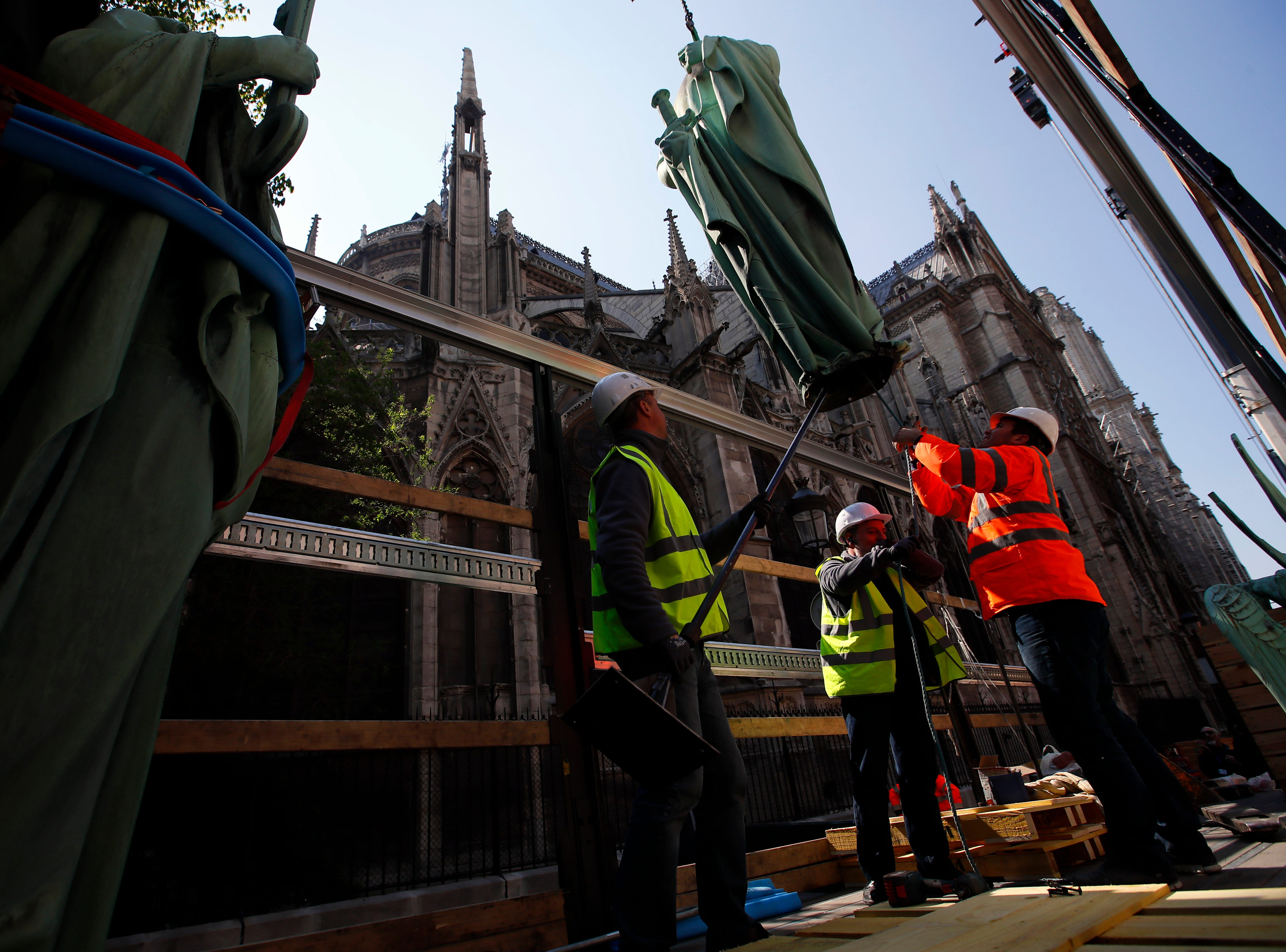 Workers secure a religious statue perched atop Paris' Notre Dame Cathedral as it descends to earth for the first time in over a century as part of a restoration, in Paris Thursday, April 11, 2019. The 16 greenish-gray copper statues, which represent the twelve apostles and four evangelists, are lowered by a 100 meter (105 yard) crane onto a truck to be taken for restoration in southwestern France.