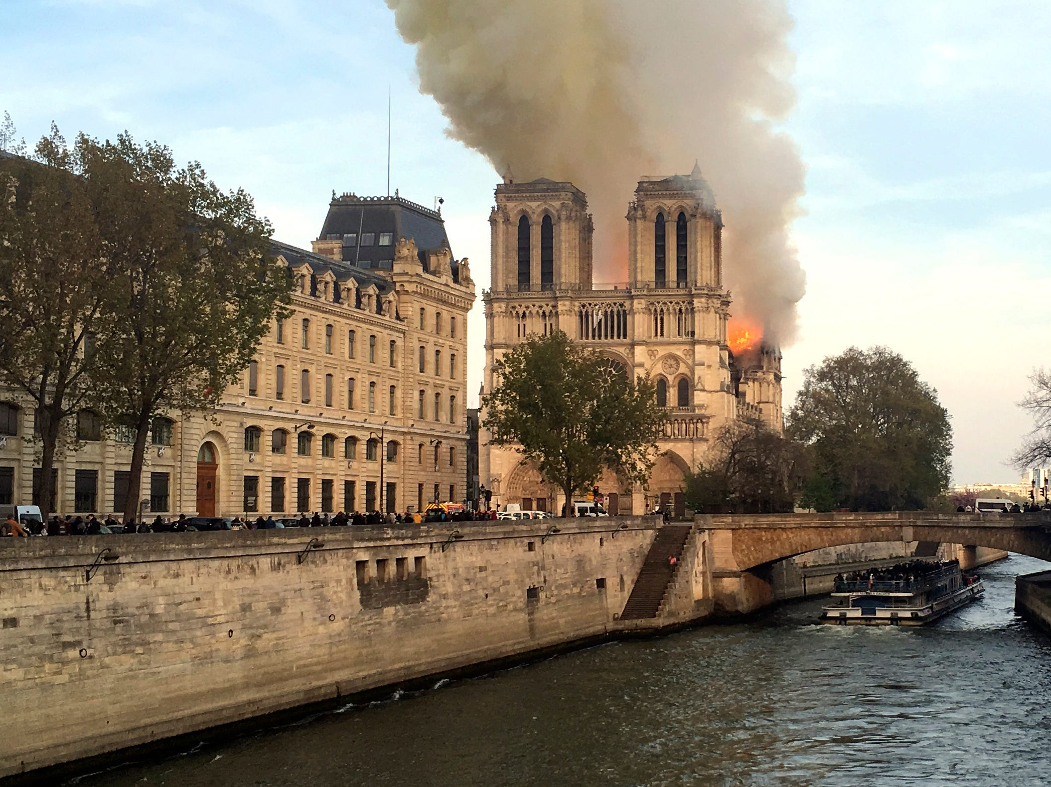 Notre Dame cathedral is burning in Paris, Monday, April 15, 2019. Massive plumes of yellow brown smoke is filling the air above Notre Dame Cathedral and ash is falling on tourists and others around the island that marks the center of Paris. (