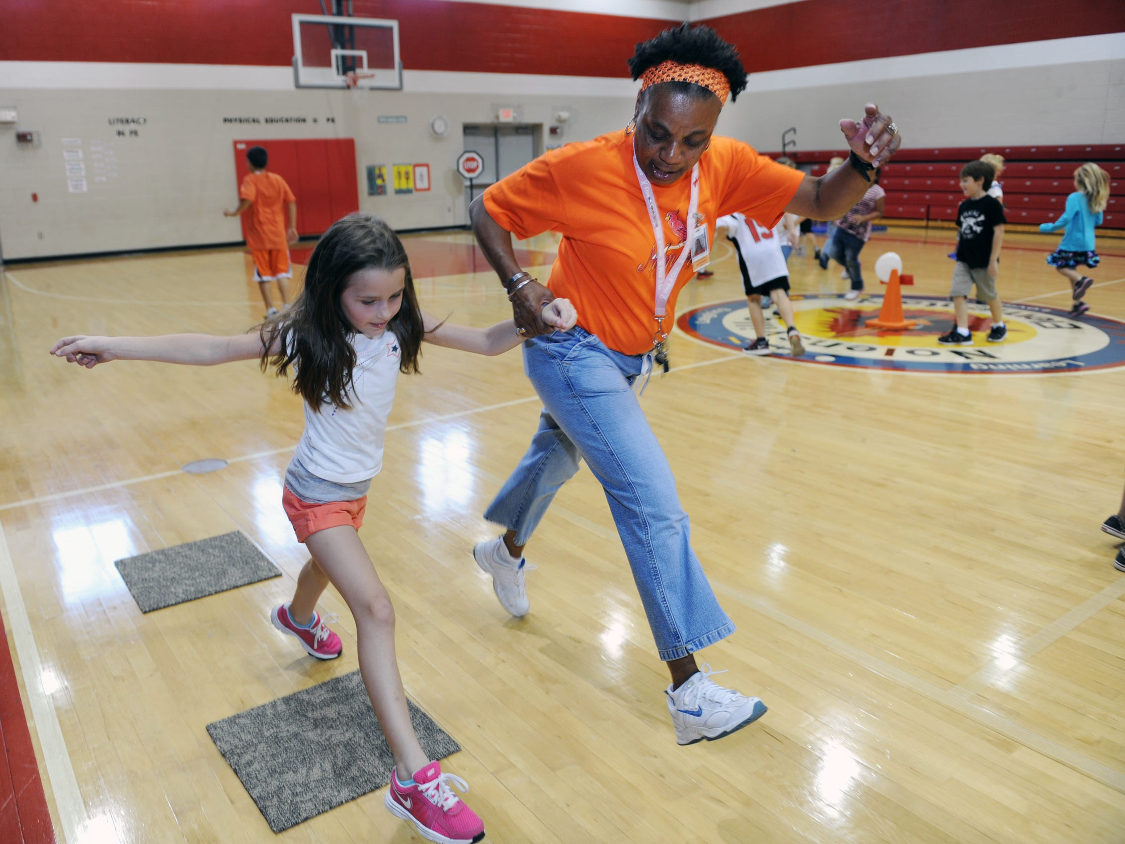 Nolensville Elementary P.E. teacher Deborah Russell, a breast cancer survivor, shows Addie Gleaves, 7, how to leap during class in 2012.
