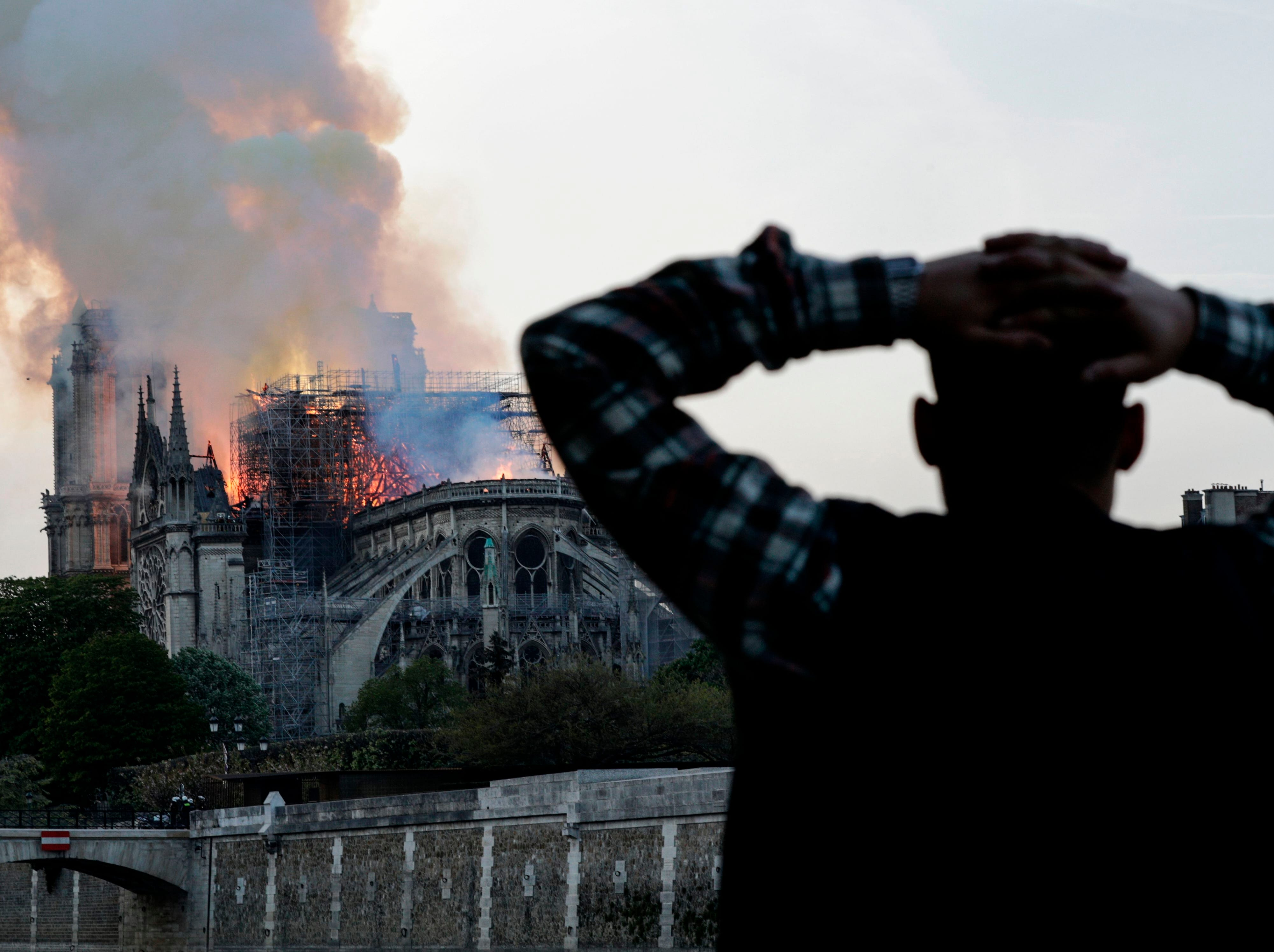 A man watches the landmark Notre-Dame Cathedral burn, engulfed in flames, in central Paris on April 15, 2019.