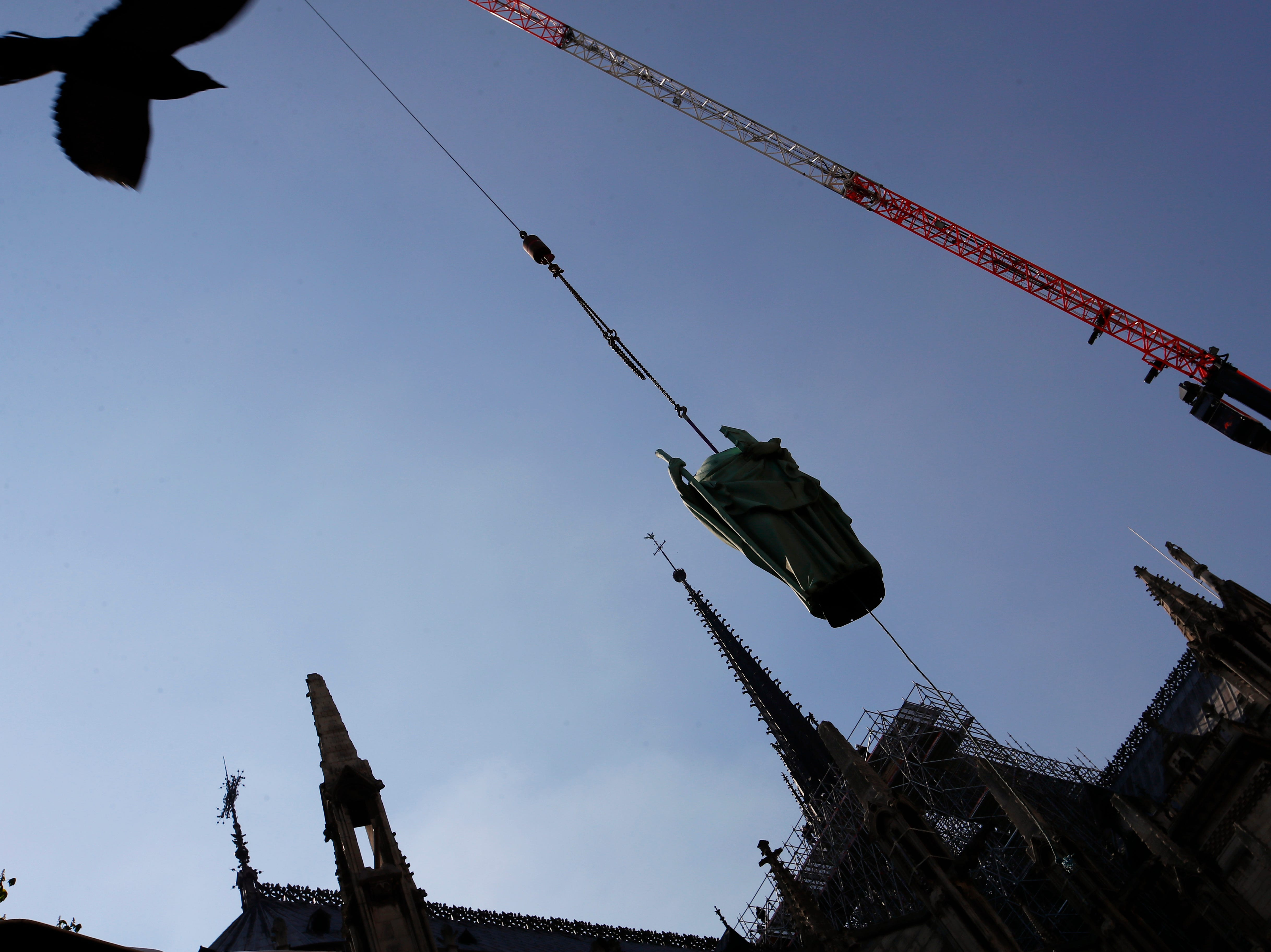 A pigeon flies over as the religious statue perched atop Paris' Notre Dame Cathedral descends to earth for the first time in over a century as part of a restoration, in Paris Thursday, April 11, 2019. The 16 greenish-gray copper statues, which represent the twelve apostles and four evangelists, are lowered by a 100 meter (105 yard) crane onto a truck to be taken for restoration in southwestern France.