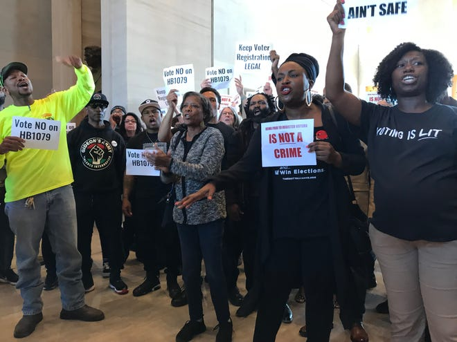 Tequila Johnson, center-right, and members of the Equity Alliance and others protest a Tennessee bill that would make changes, including adding criminal penalties, to Tennessee's voter registration process.
