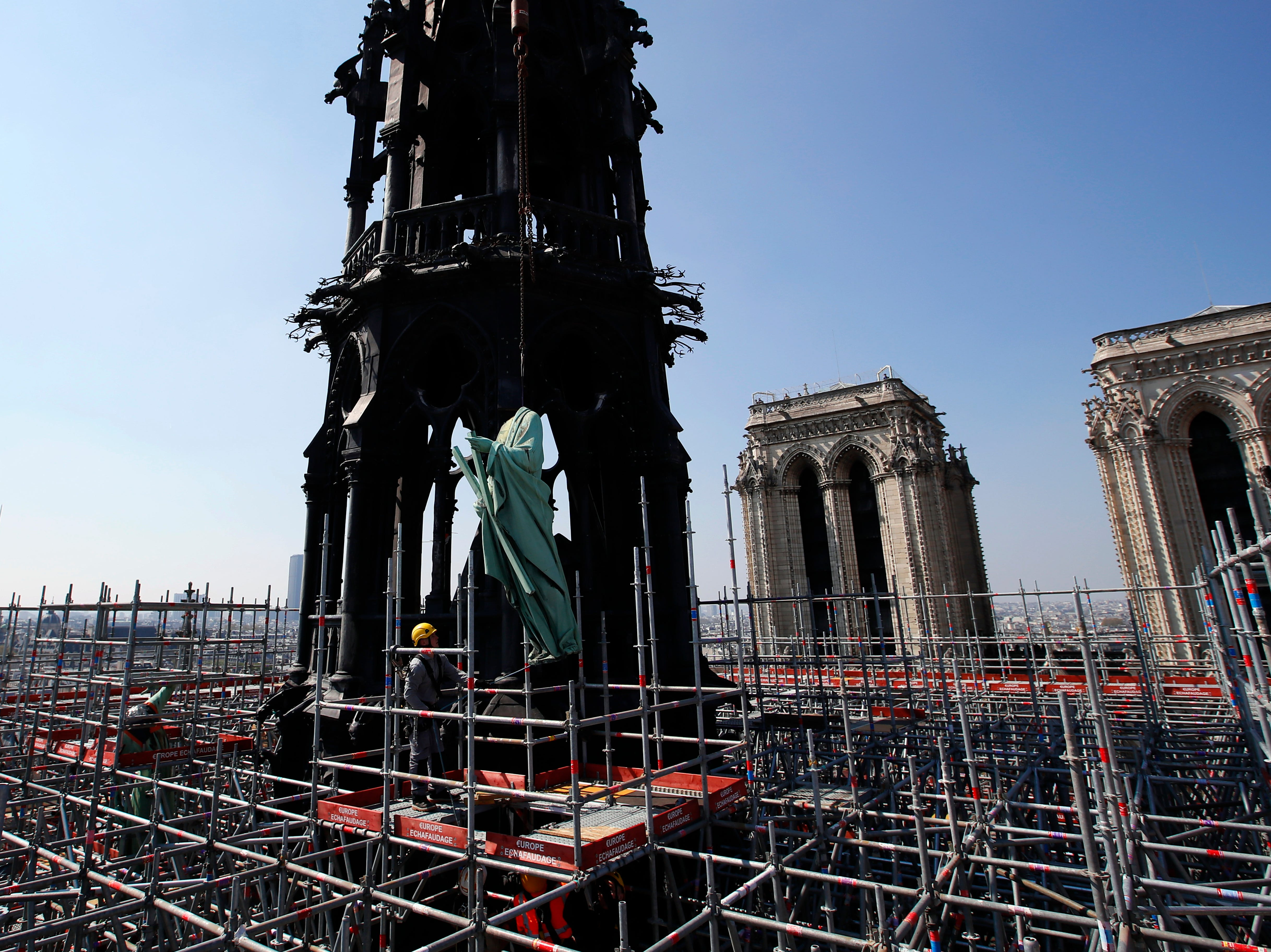 The religious statue representing St. Andrew perched atop Paris' Notre Dame Cathedral descends to earth for the first time in over a century as part of a restoration, in Paris Thursday, April 11, 2019. The 16 greenish-gray copper statues, which represent the twelve apostles and four evangelists, are lowered by a 100 meter (105 yard) crane onto a truck to be taken for restoration in southwestern France.