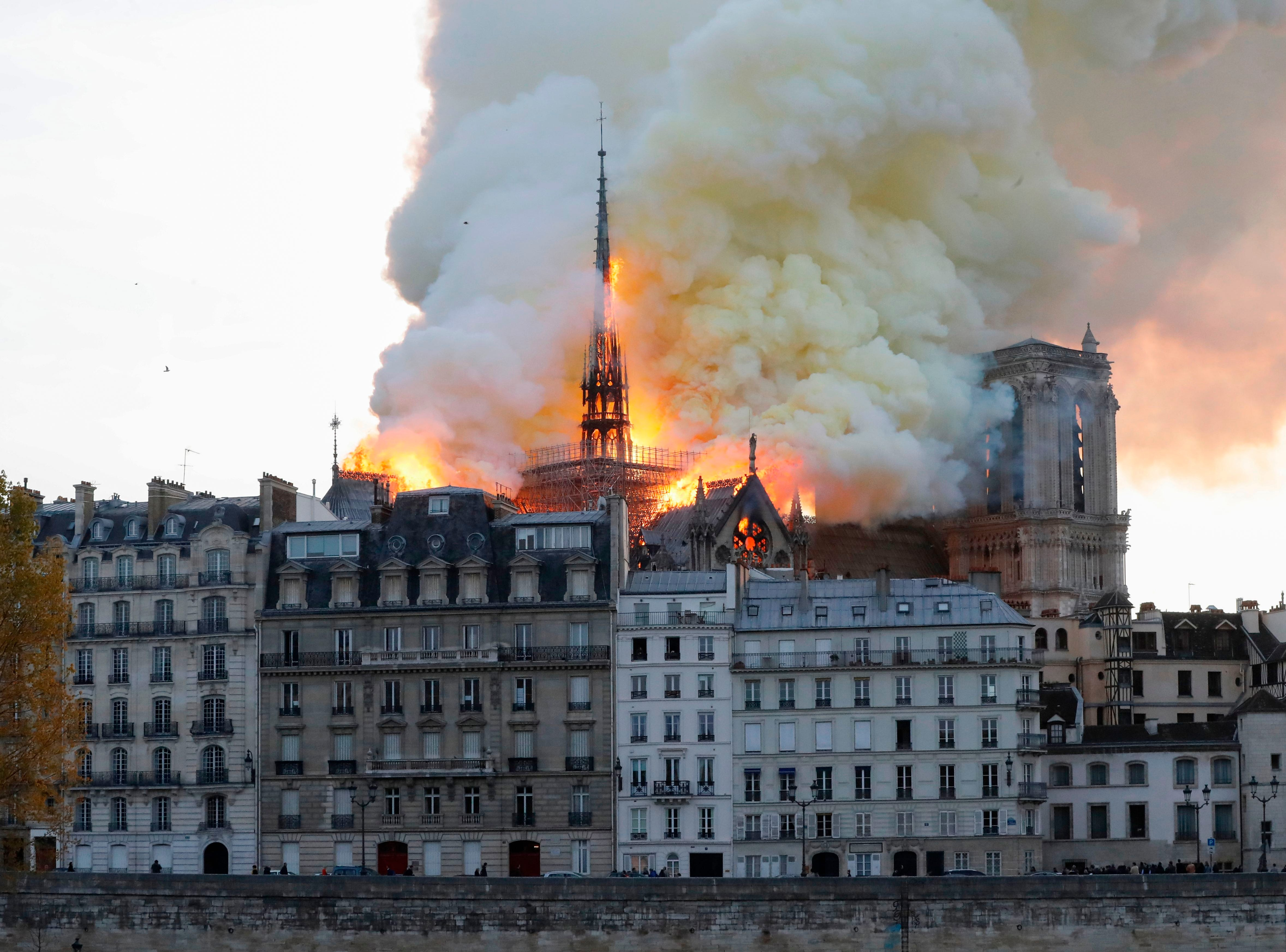 Seen from across the Seine River, smoke and flames rise during a fire at the landmark Notre-Dame Cathedral in central Paris on April 15, 2019, potentially involving renovation works being carried out at the site, the fire service said.