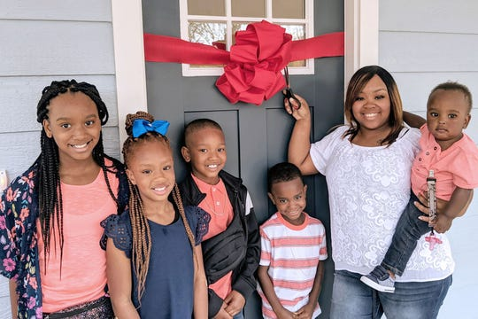 Jamesia Dowell cuts the ribbon to her new home April 13, 2019. She will buy the home next month with an affordable mortgage from Habitat for Humanity Williamson-Maury.