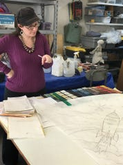 One of the lead artists, Susan Prado, working out the tile selection for the Mosaic Marathon chair design.