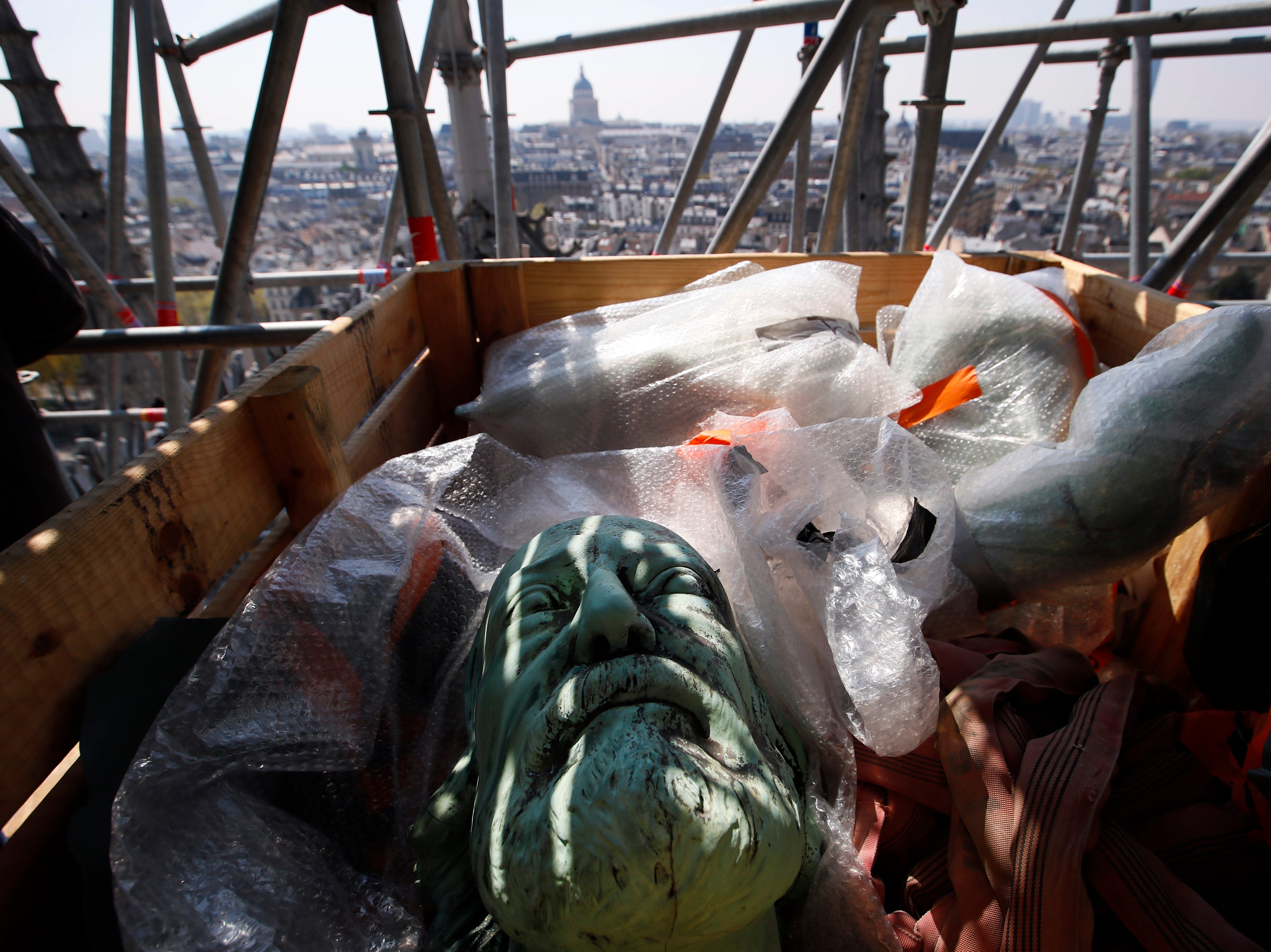 The head of a religious statue representing St. Thomas atop Paris' Notre Dame Cathedral is loaded in a box prior to descend to earth for the first time in over a century as part of a restoration, in Paris Thursday, April 11, 2019. The 16 greenish-gray copper statues, which represent the twelve apostles and four evangelists, are lowered by a 100 meter (105 yard) crane onto a truck to be taken for restoration in southwestern France.