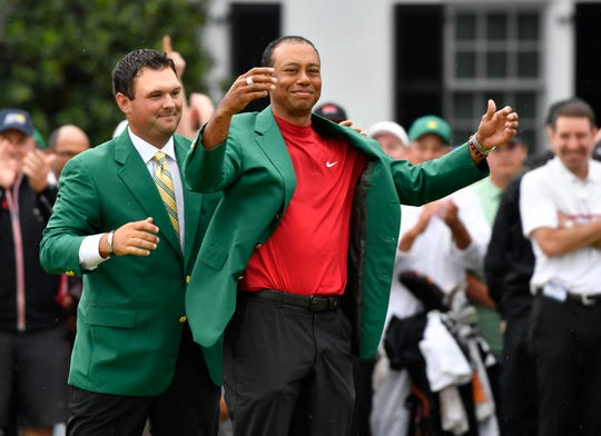 2018 winner Patrick Reed places the green jacket on 2019 winner Tiger Woods after the final round of The Masters golf tournament at Augusta National Golf Club on Sunday in Augusta, Ga.
