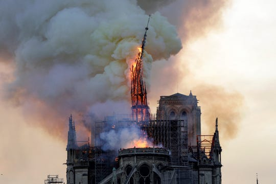 The steeple of the landmark Notre-Dame Cathedral collapses as the cathedral is engulfed in flames in central Paris on April 15, 2019.  A huge fire swept through the roof of the famed Notre-Dame Cathedral in central Paris on April 15, 2019, sending flames and huge clouds of grey smoke billowing into the sky. The flames and smoke plumed from the spire and roof of the gothic cathedral, visited by millions of people a year. A spokesman for the cathedral told AFP that the wooden structure supporting the roof was being gutted by the blaze.