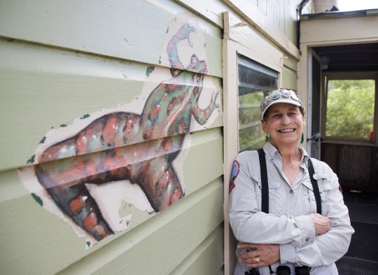 Audubon Corkscrew Swamp Sanctuary volunteer Leslie Burgess stands Wednesday, April 10, 2019, next to a painting of a frog she painted on the volunteers' Bunting House in the late 90s. Burgess, a longtime volunteer, was recently honored for a special service project. She painted animals on fragments of boardwalk damaged in Hurricane Irma. The paintings raised over $8,000 to help pay for boardwalk repairs at the sanctuary.
