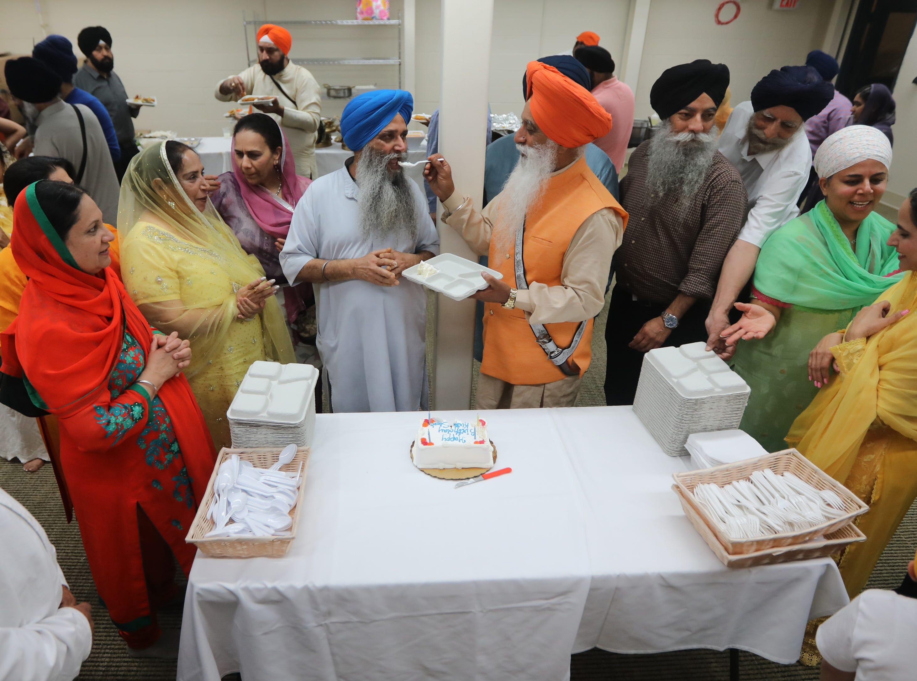 People, including, Chairman of the Board, Amrik Singh Sikland  (orange turban), line up to feed, Priest Kirtan Singh (blue turban) his birthday cake.  Sunday, April, 14, 2019