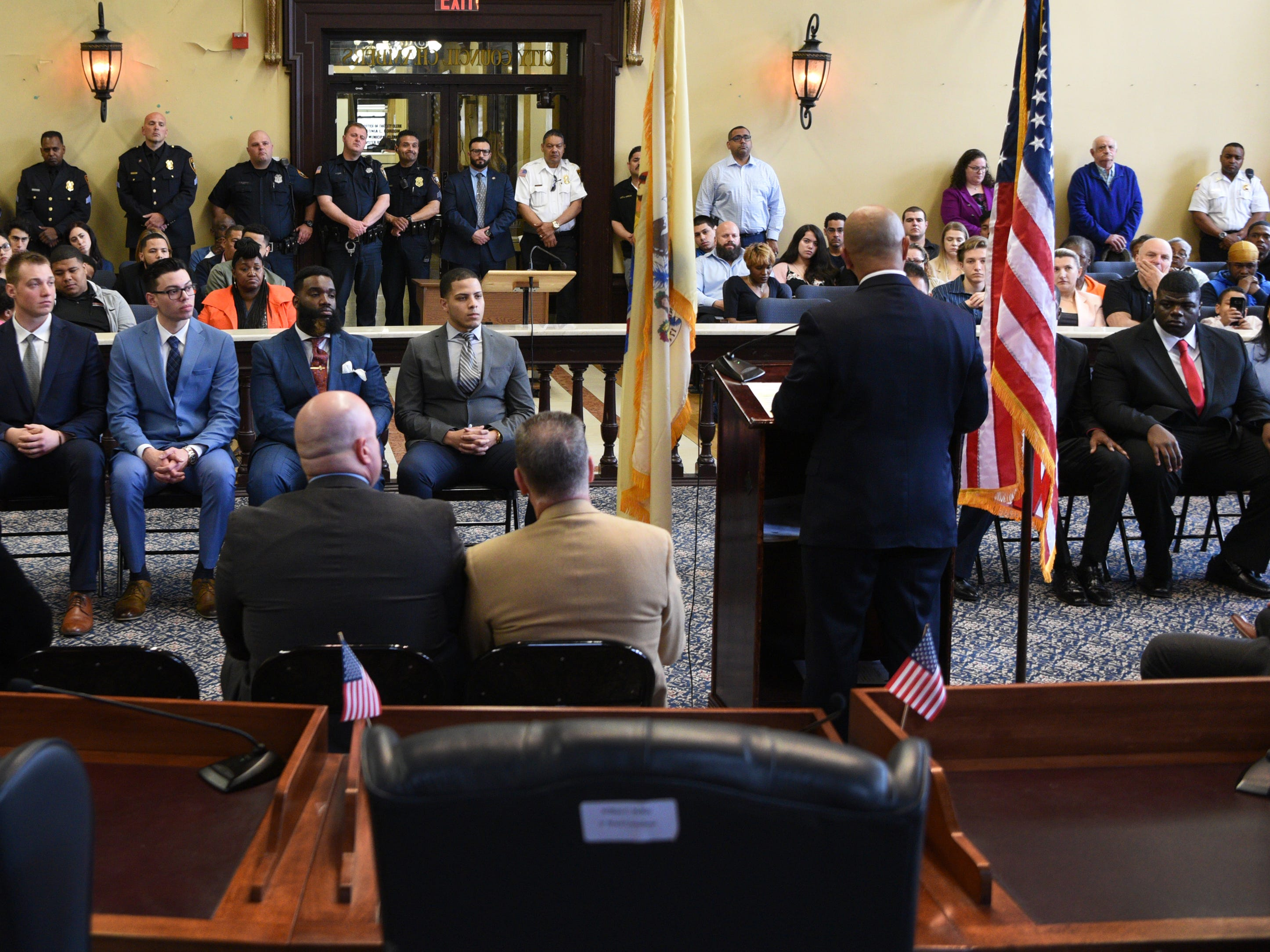 Eight new Paterson police officers, seated, listen to an address by Det. Alex Cruz, Paterson PBA presideint, during their swearing-in ceremony at Paterson City Hall on Monday, April 14, 2019.