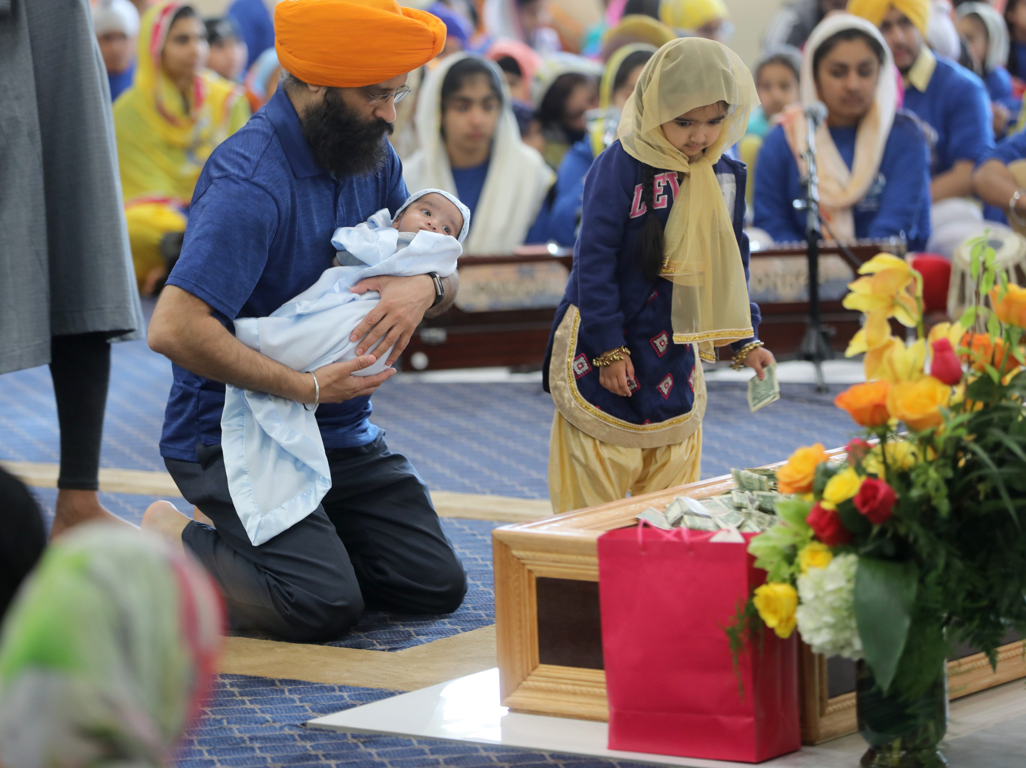 People kneel to pray and give a monetary donation at the  Guru Nanak Mission. Sunday, April, 14, 2019