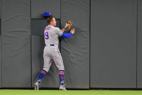 Apr 14, 2019; Atlanta, GA, USA; New York Mets center fielder Brandon Nimmo (9) runs into the wall after catching a ball hit by Atlanta Braves second baseman Ozzie Albies (not shown) during the fourth inning at SunTrust Park.